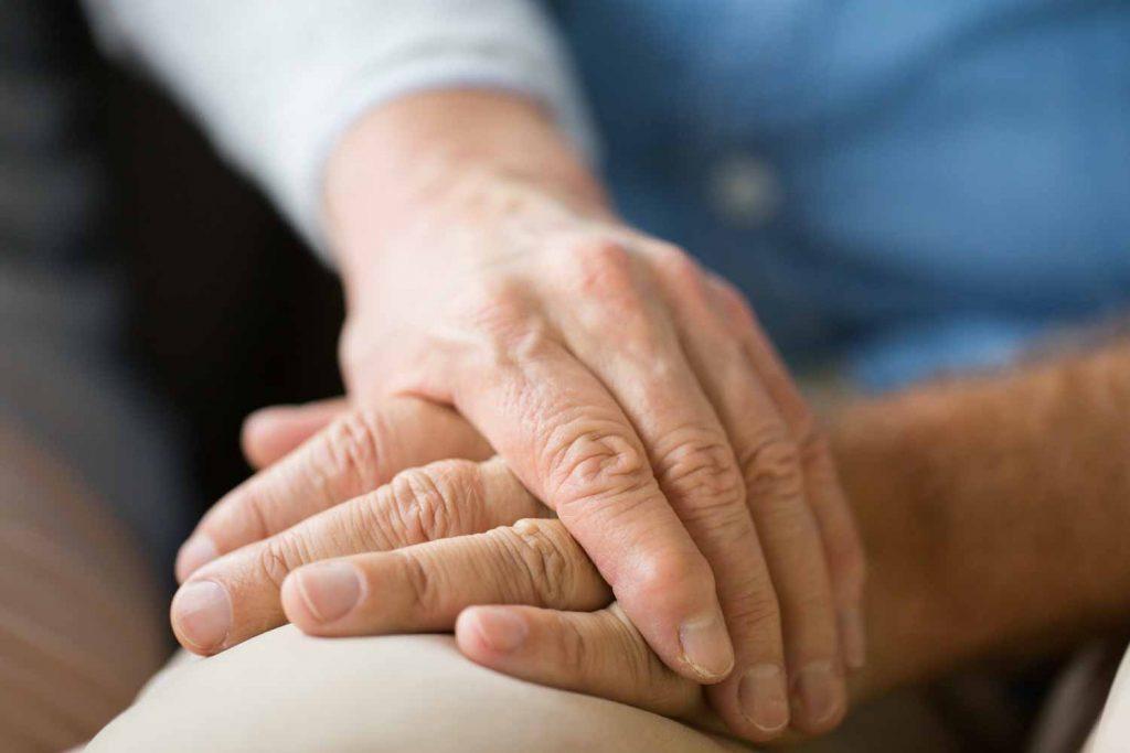 Frau hält Hand von krankem Mann